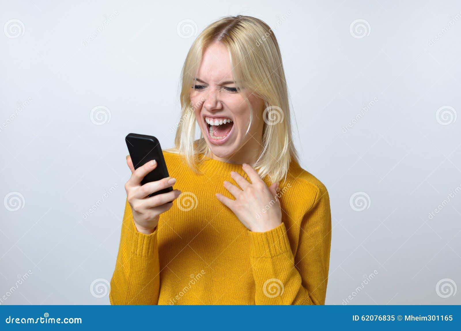 Mujer joven chocada que mira su teléfono móvil