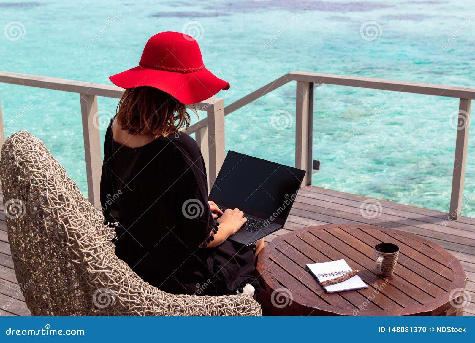 Mujer joven con el funcionamiento rojo del sombrero en un ordenador en un destino tropical
