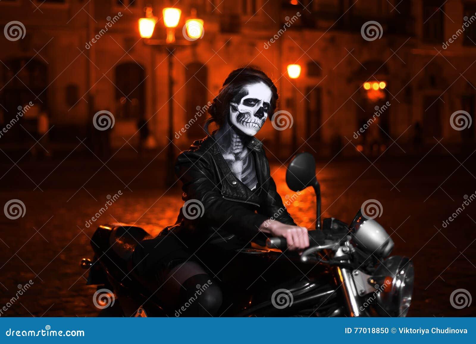 Mujer joven con el maquillaje de Halloween que se sienta en la moto Retrato de la calle