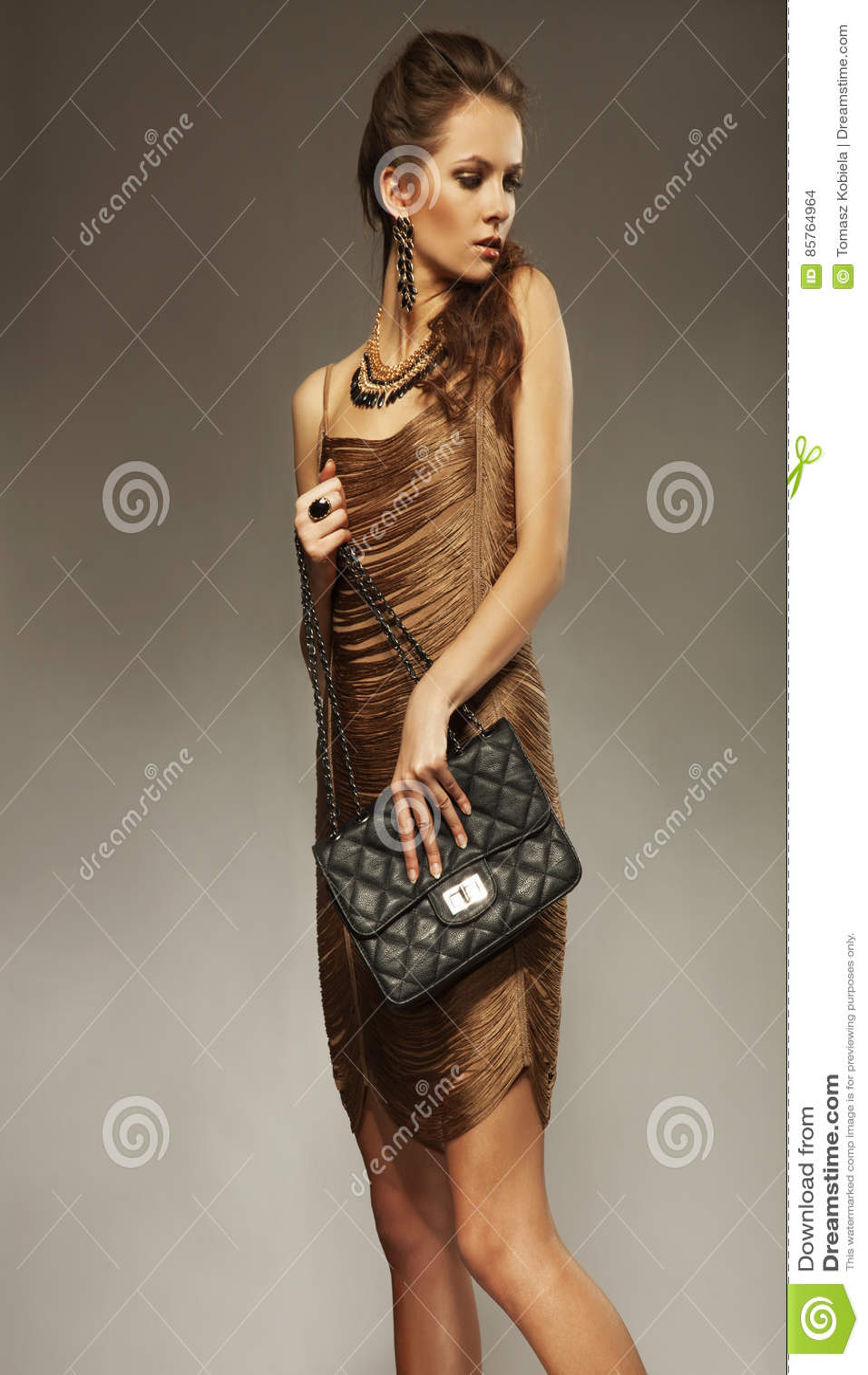Mujer joven con el pelo, vestido del oro y joyería y handb fijados