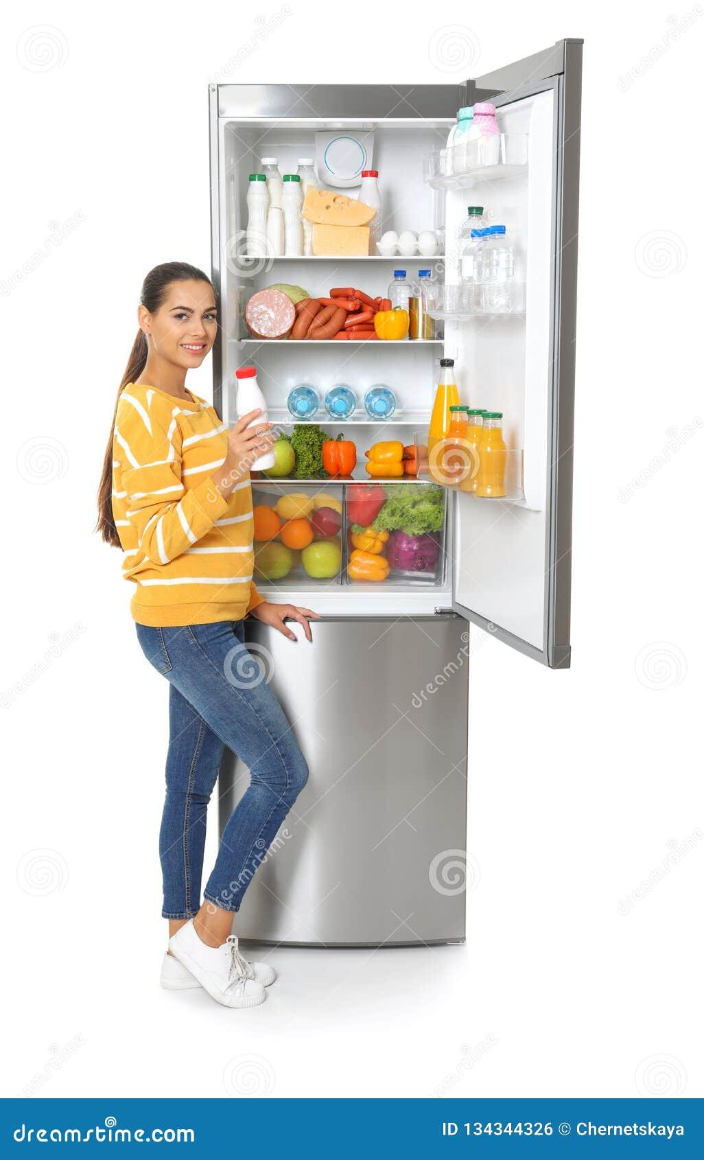 Mujer joven con la botella del yogur de refrigerador abierto cerca