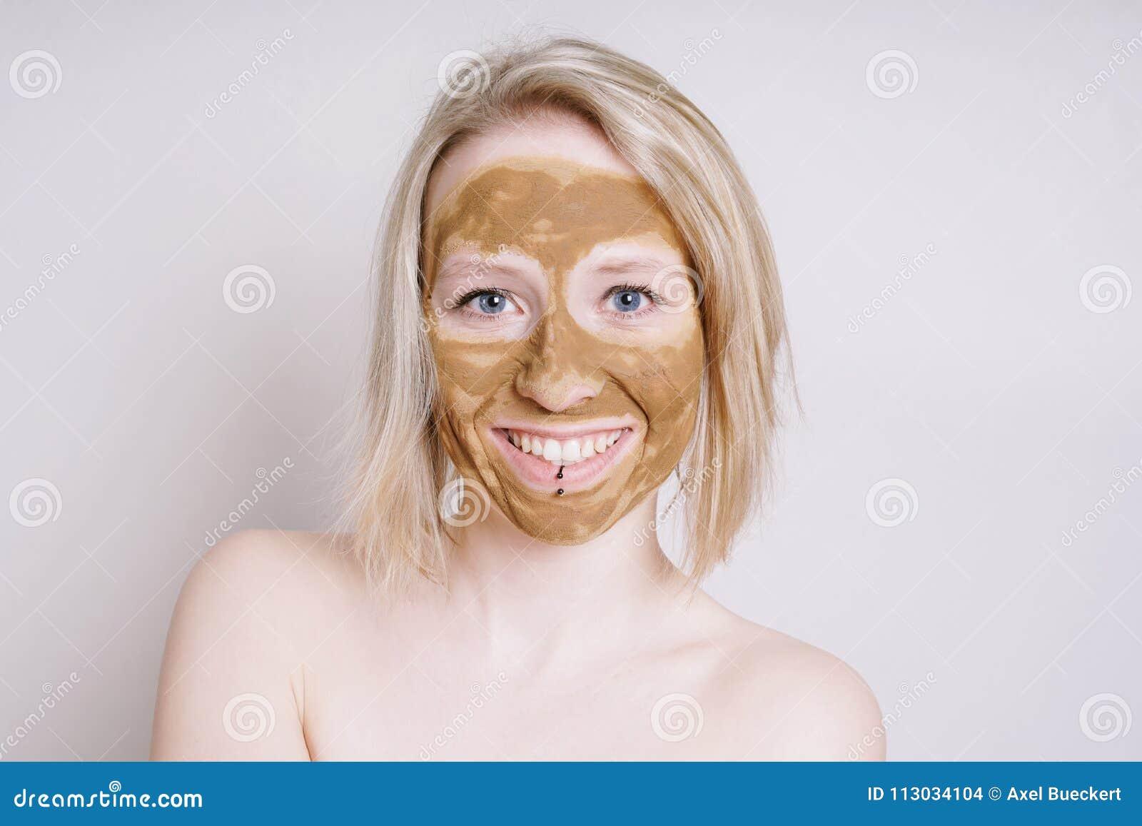 Mujer joven con la máscara facial curativa de la belleza de la tierra o de la arcilla