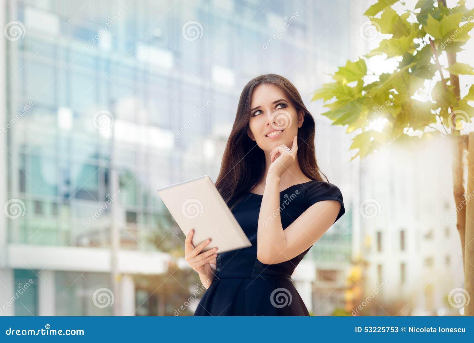 Mujer joven con la tableta hacia fuera en la ciudad