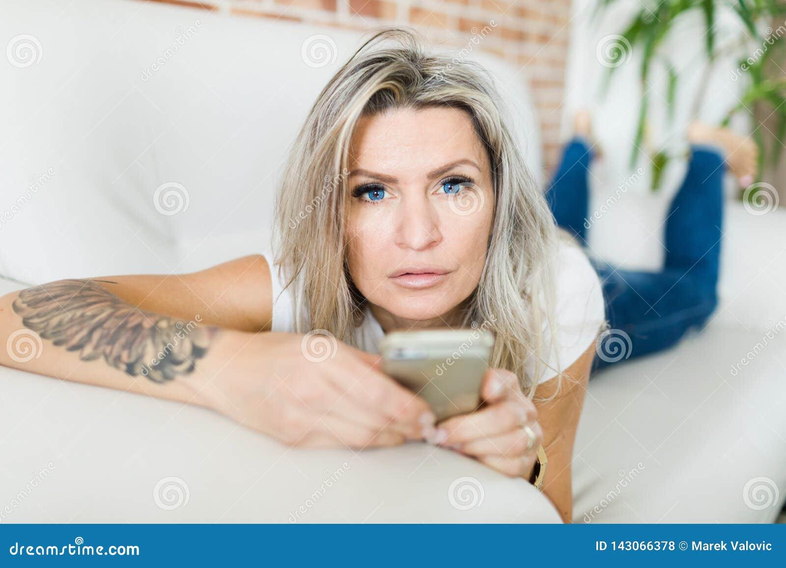 Mujer joven con las lentes de contacto azules usando el teléfono elegante