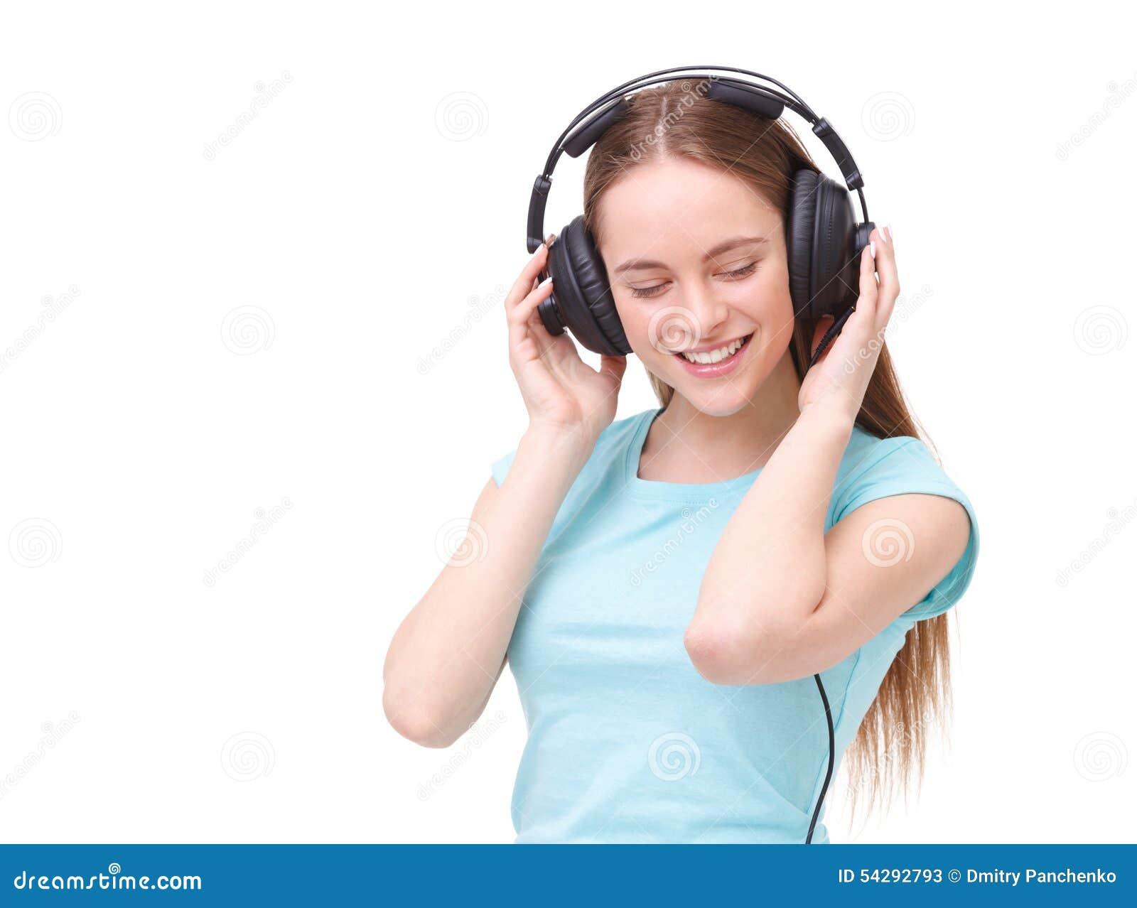Mujer joven con los auriculares que escucha la música y el baile