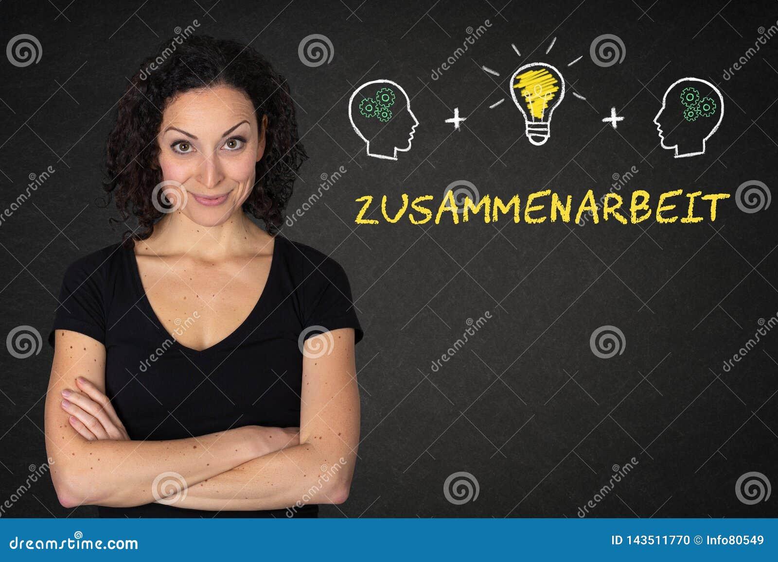 Mujer joven con los brazos, las cabezas, la bulbo-idea y el texto cruzados 'Zusammenarbeit 'en una pizarra Traducción: y x27; Tea