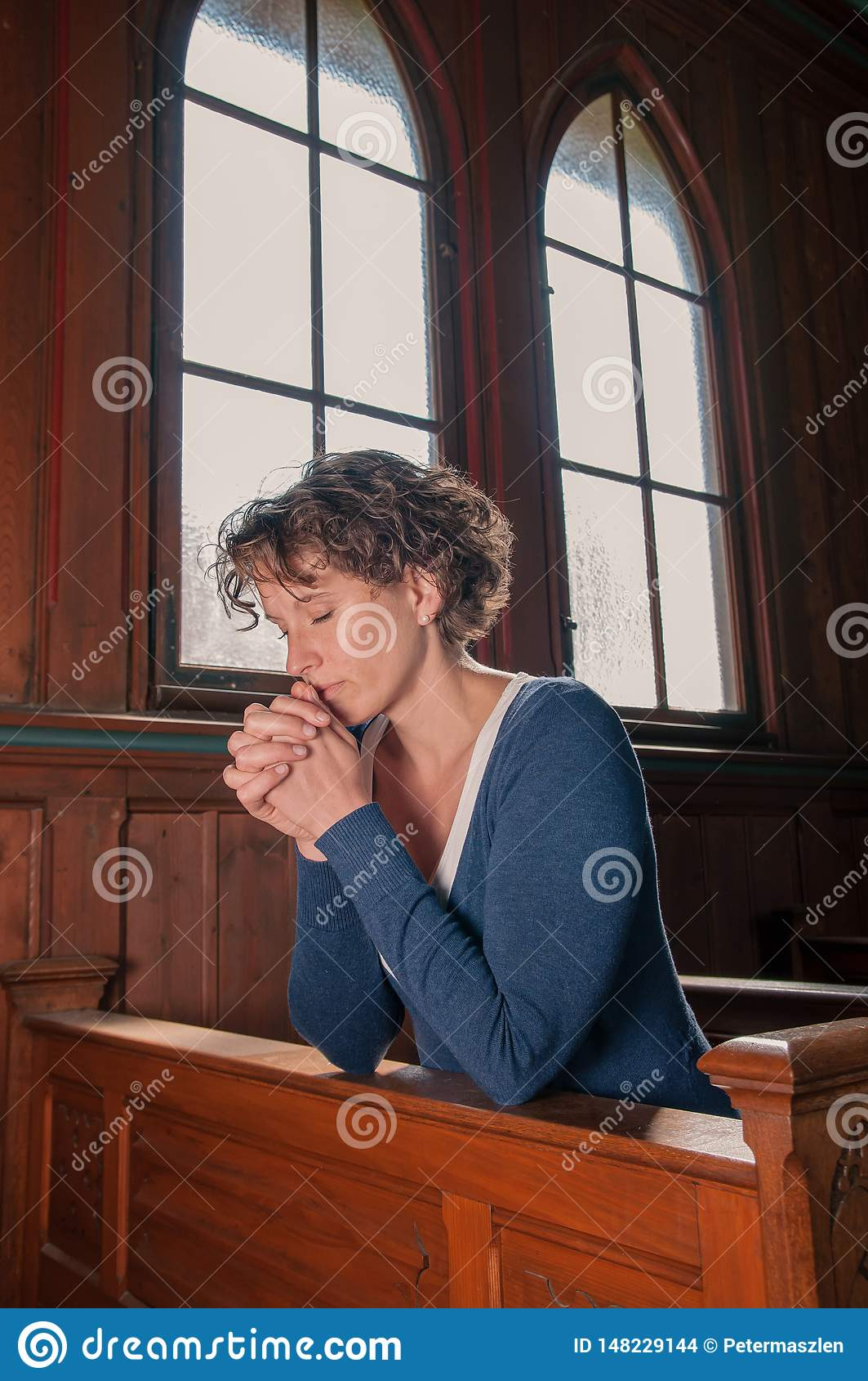 Mujer joven con los ojos cerrados que ruega en la iglesia