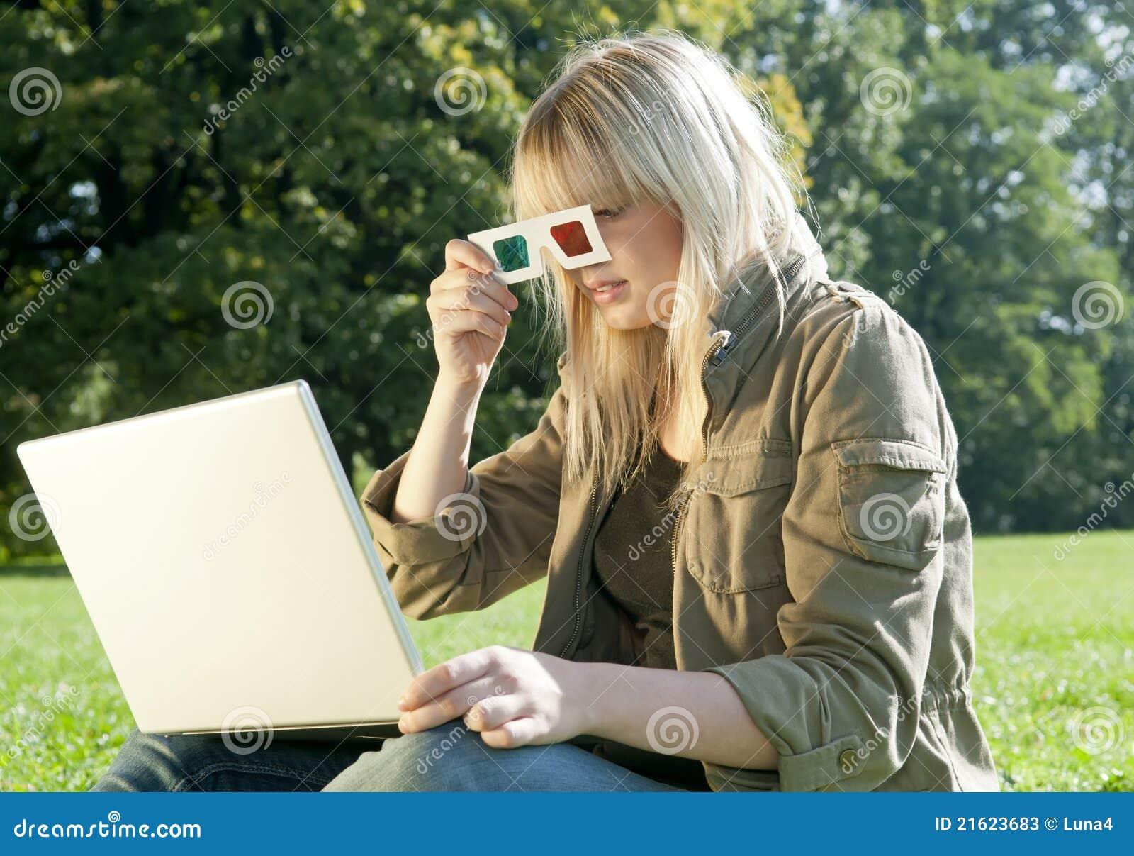 Mujer joven con los vidrios 3D y la computadora portátil
