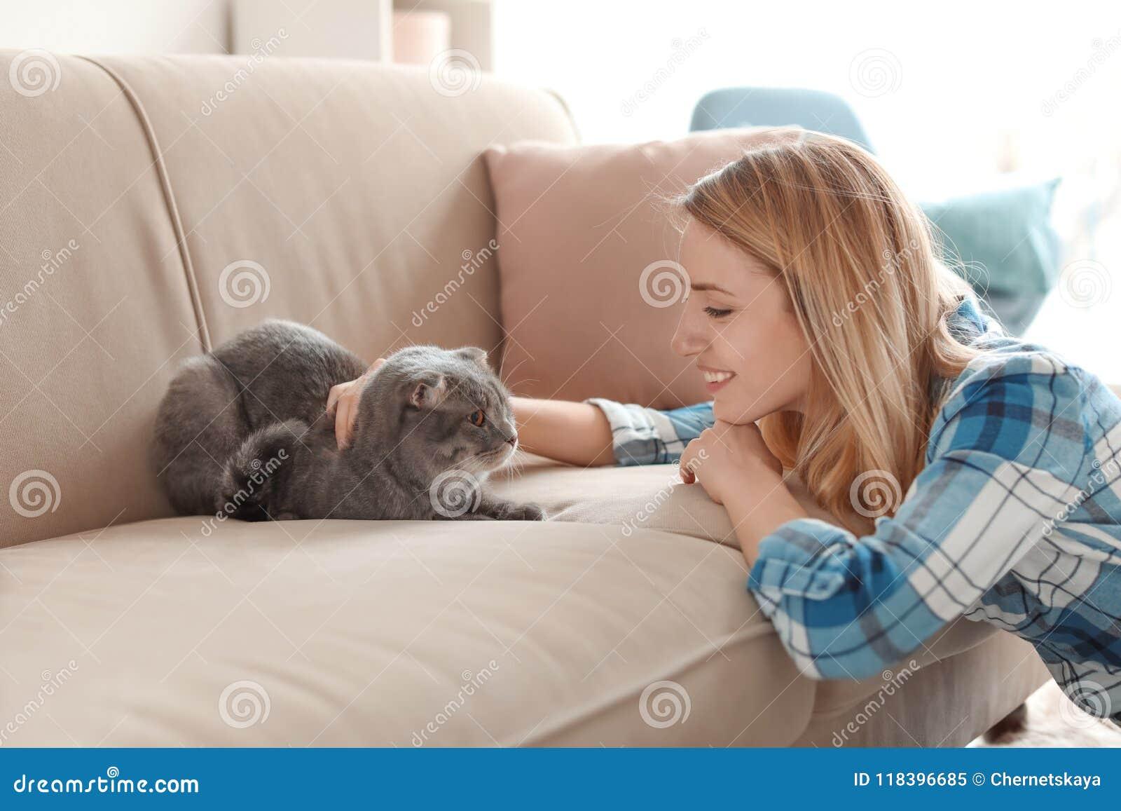 Mujer joven con su gato del animal doméstico en casa