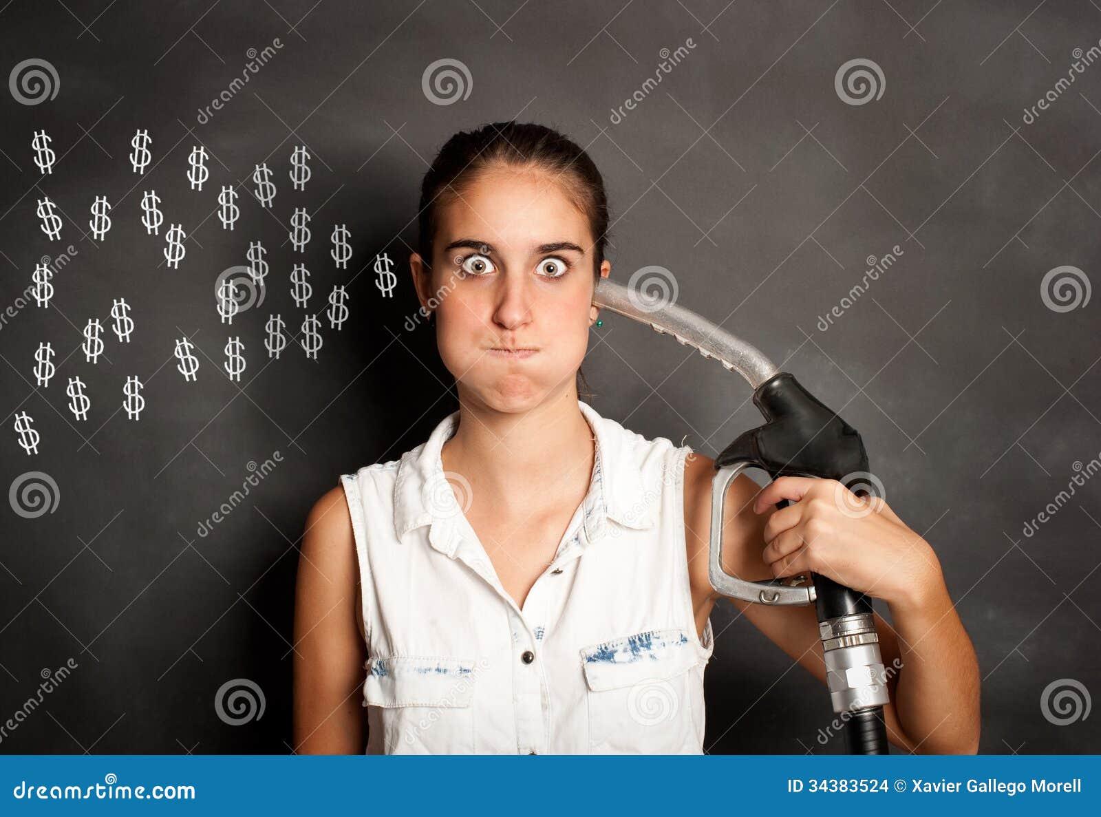 Mujer joven con una boca del surtidor de gasolina