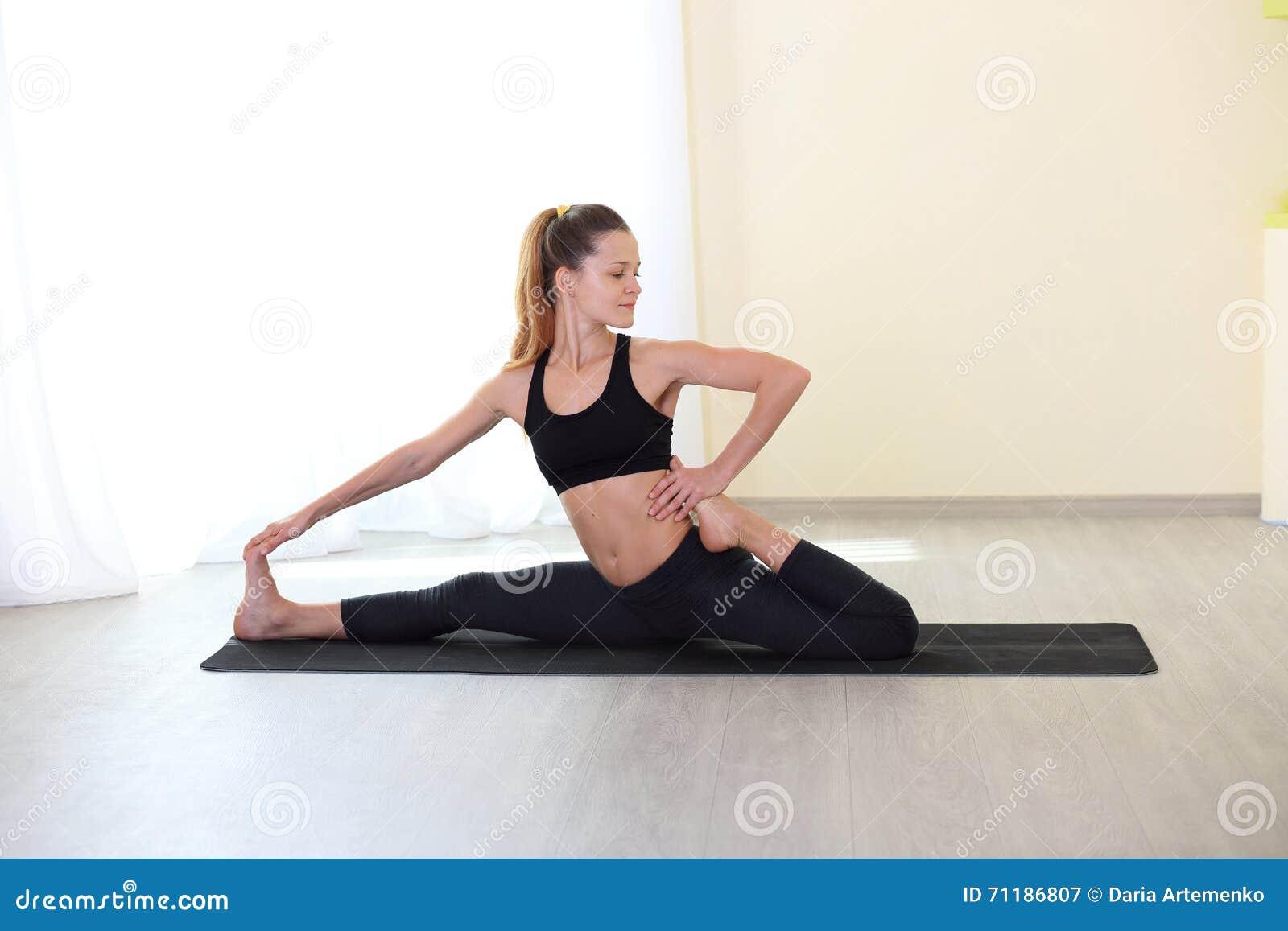 Mujer joven de la aptitud que hace el ejercicio de Pilates en el gimnasio