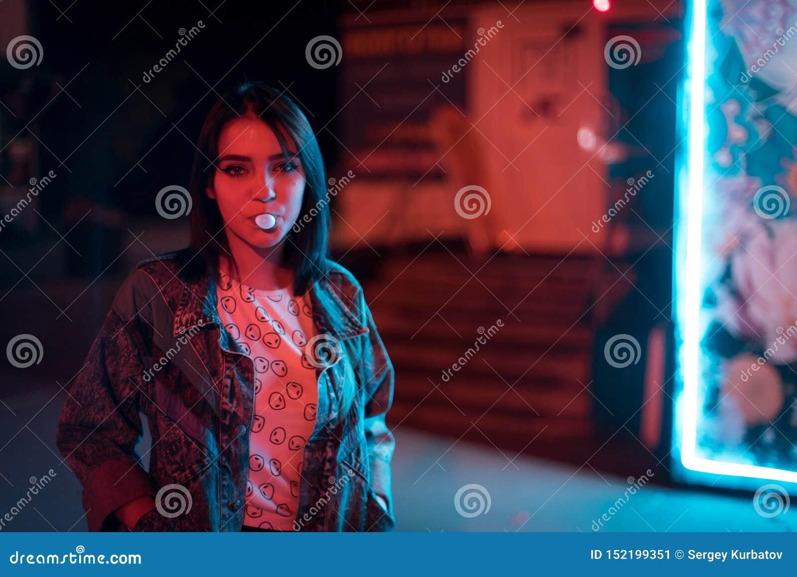 Mujer joven de la moda joven en el chicle que sopla de los vidrios de la piel iluminado con la muestra rosada azul de neón de la