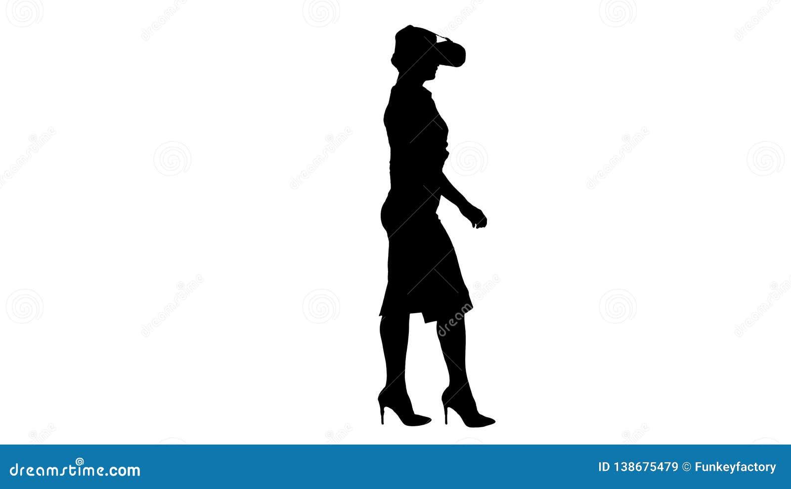 Mujer joven de la silueta que lleva el dispositivo y caminar de la realidad virtual