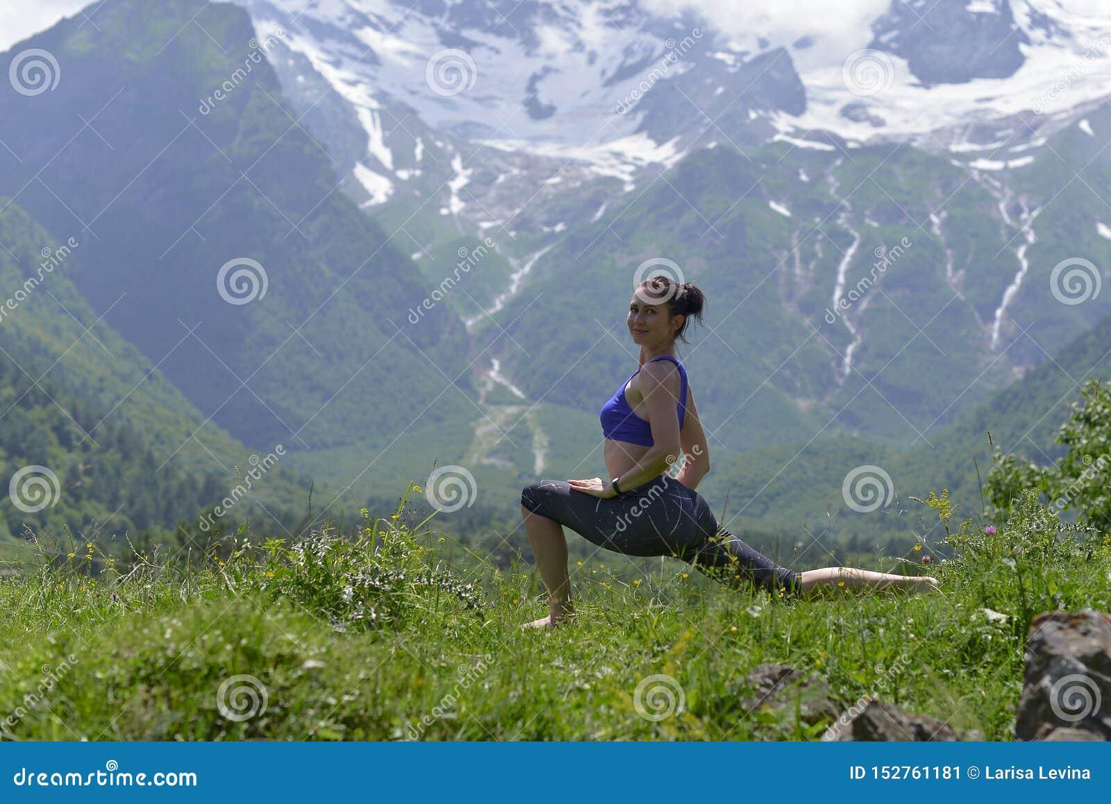 Mujer joven de los deportes que hace yoga en la hierba verde en el verano