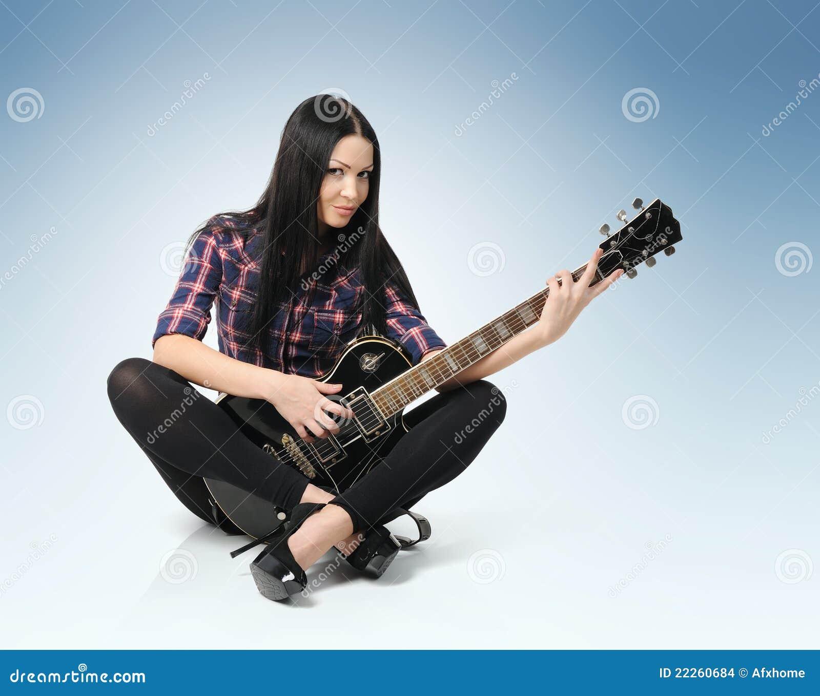Mujer joven de moda atractiva con la guitarra