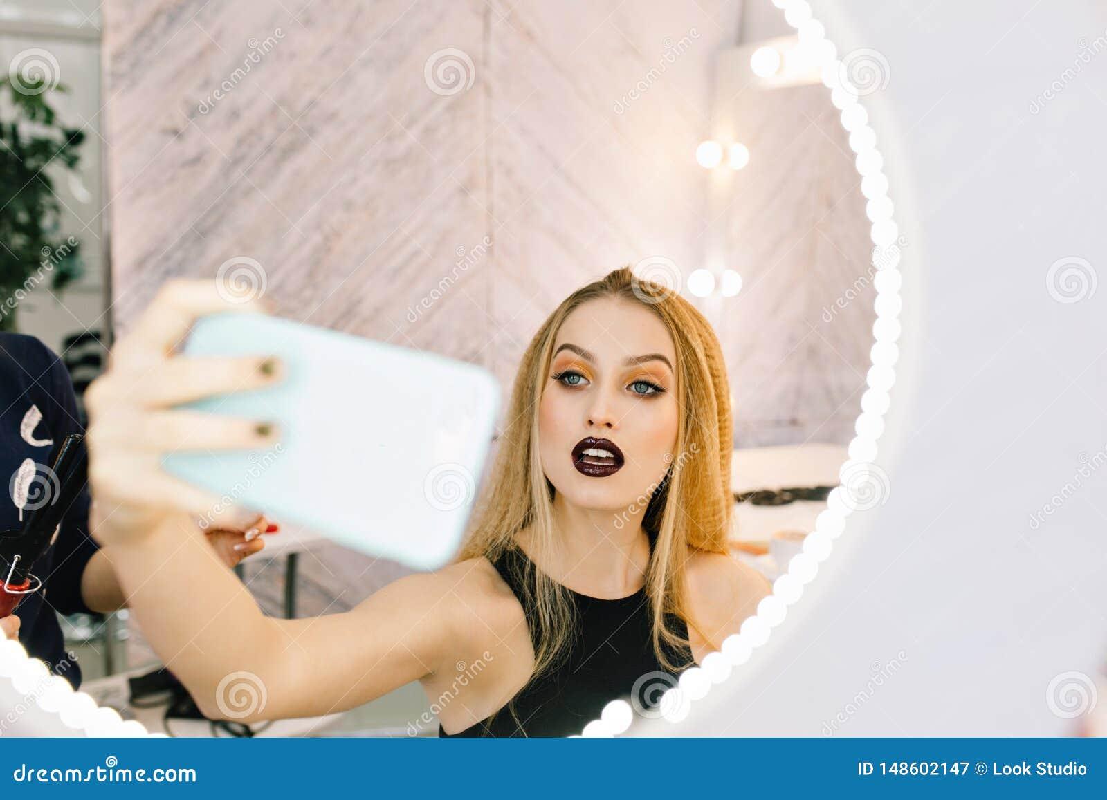 Mujer joven de moda del encanto del retrato con el pelo rubio largo que hace el selfie en espejo en sal?n del peluquero Elegante