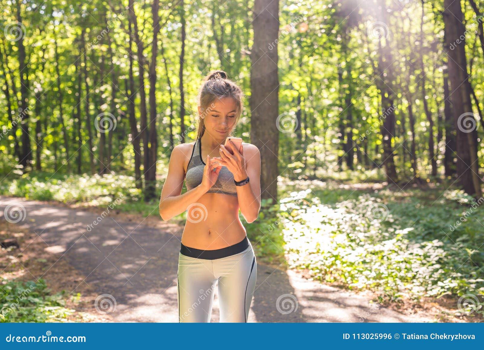 Mujer joven del atleta que comprueba progreso de la aptitud en cuanto a su reloj elegante Corredor femenino que usa la aptitud ap