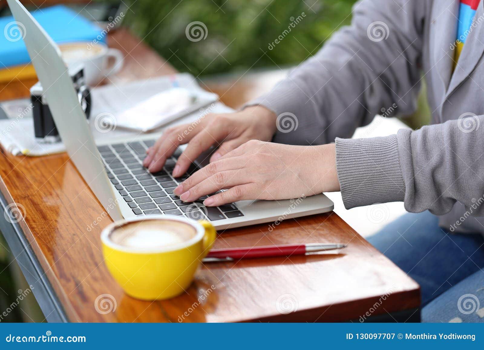 Mujer joven del freelancer que trabaja usando el ordenador portátil en coffe