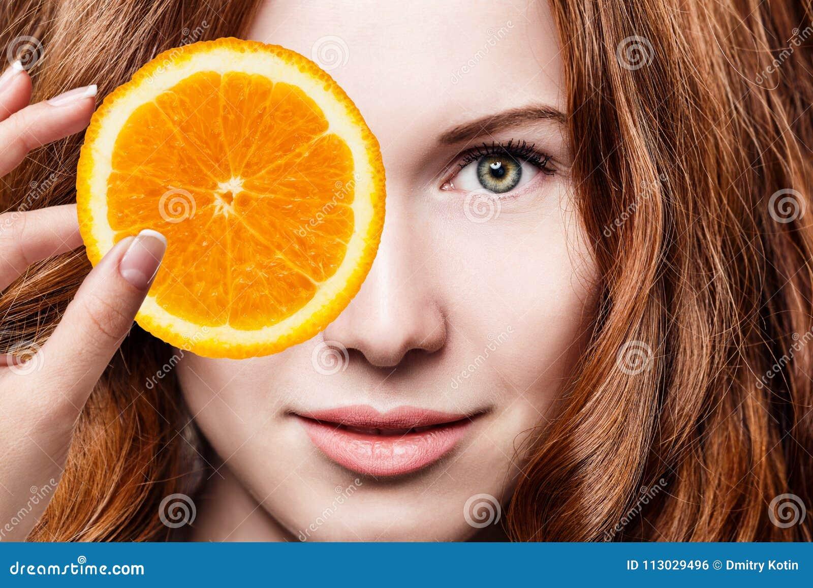 Mujer joven del pelirrojo con las rebanadas anaranjadas de la fruta