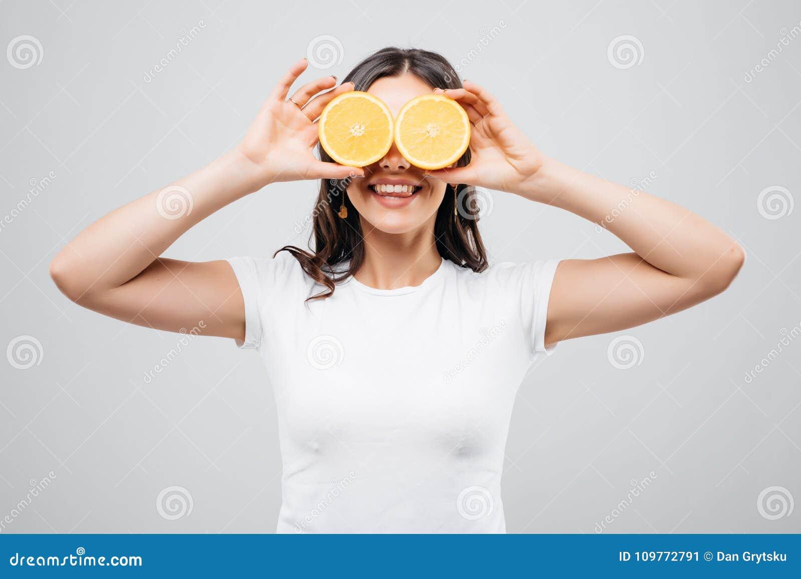 Mujer joven del primer hermoso con las naranjas aisladas en el fondo blanco Concepto sano del alimento Cuidado y belleza de piel
