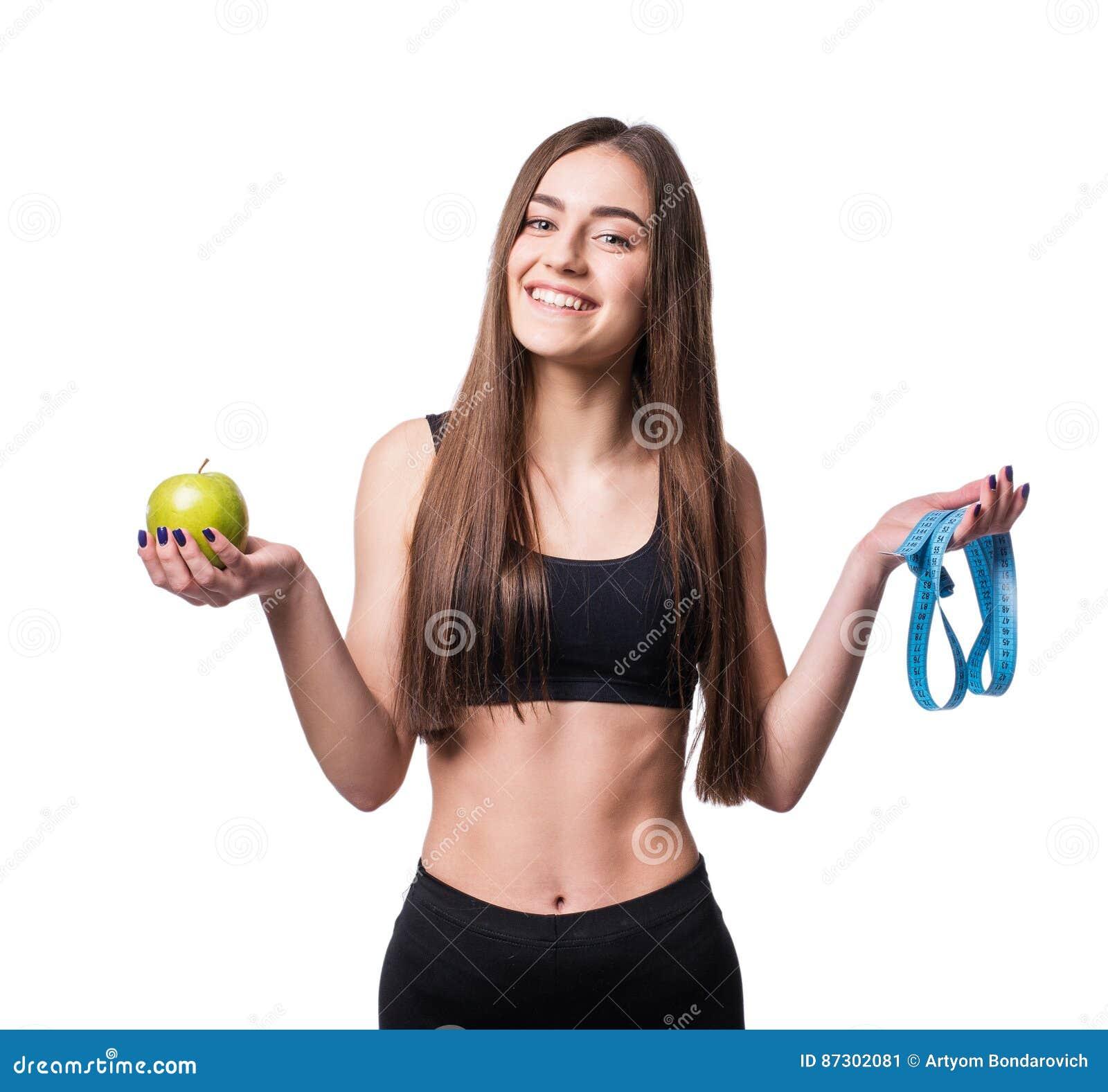 Mujer joven delgada y sana que sostiene la cinta de la medida y manzana aislada en el fondo blanco Pérdida de peso y concepto de