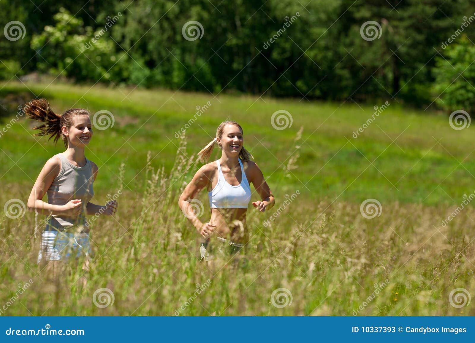 Mujer joven dos que activa en un prado