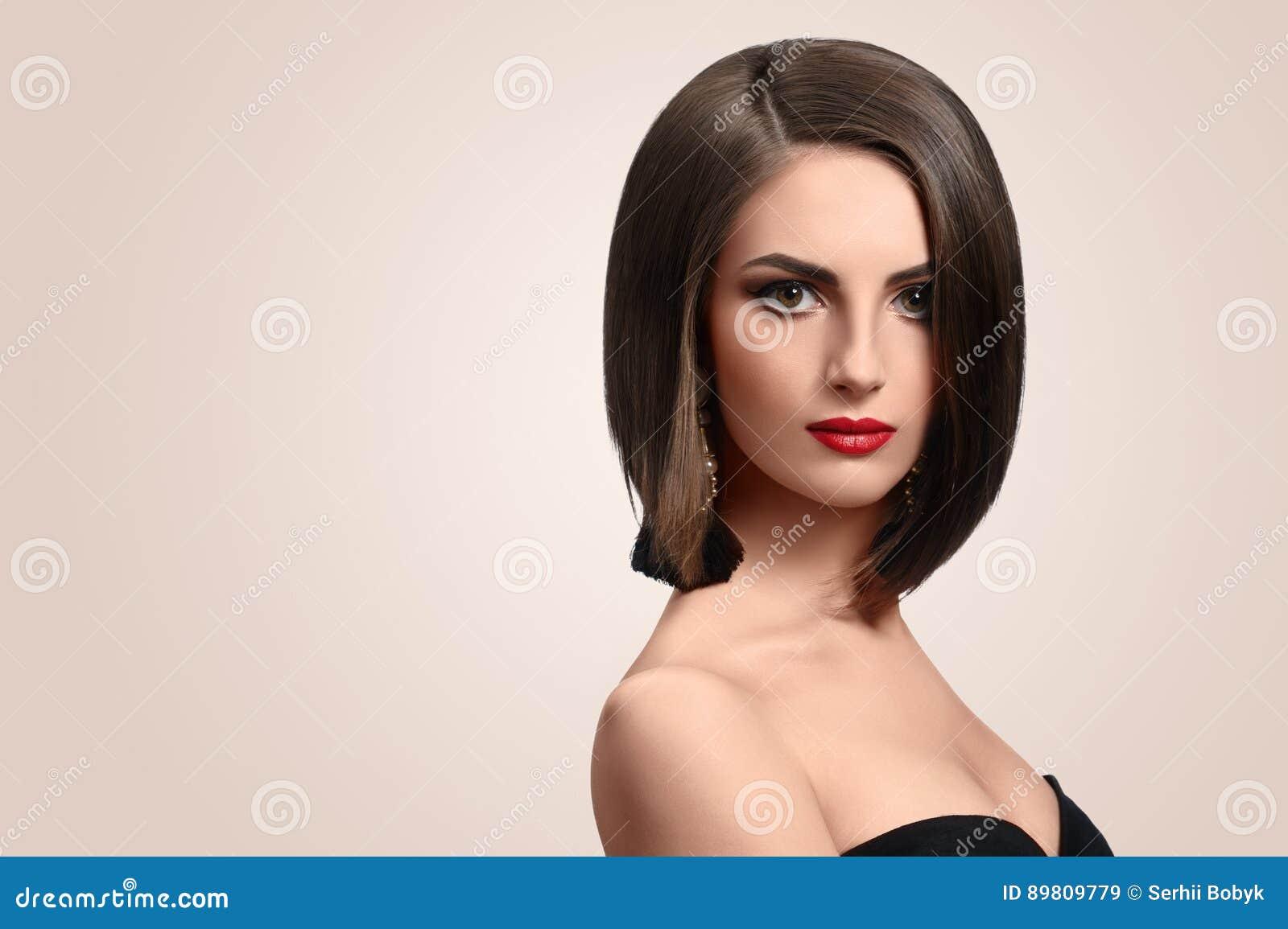 Mujer joven elegante hermosa que presenta en estudio