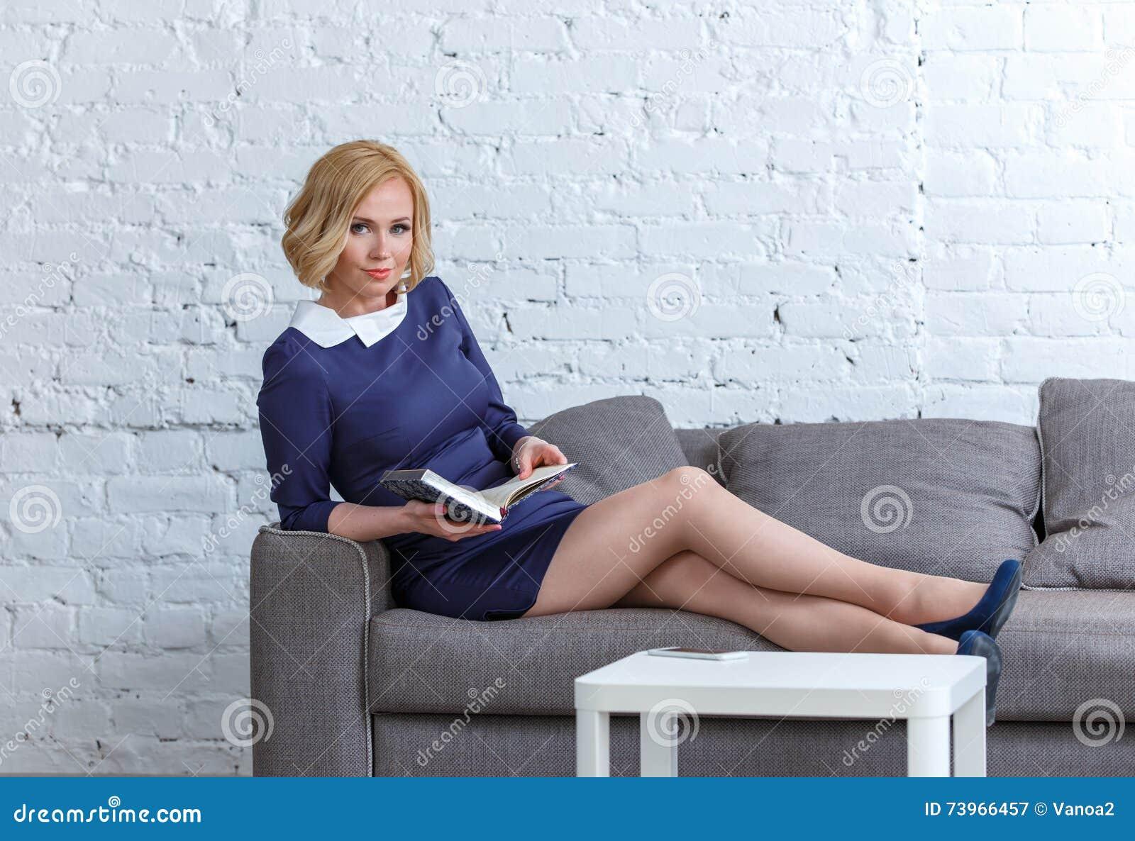 Mujer joven elegante que miente en un sofá cómodo con su diario