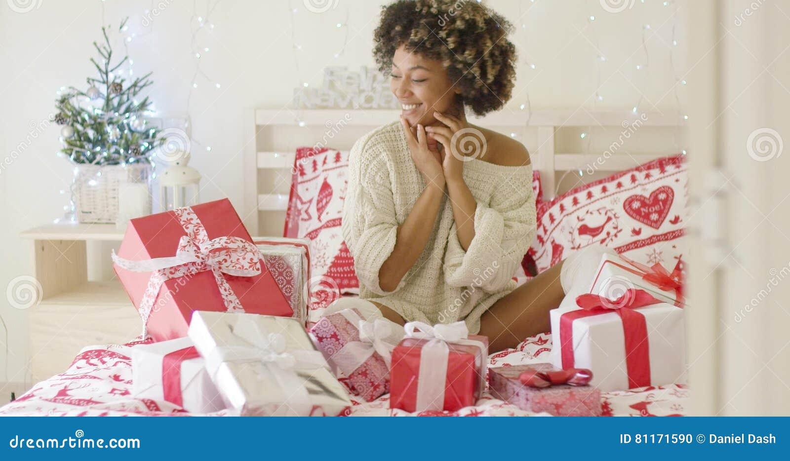 974b2535241a Mujer joven emocionada con una cama llena de regalos de Navidad.