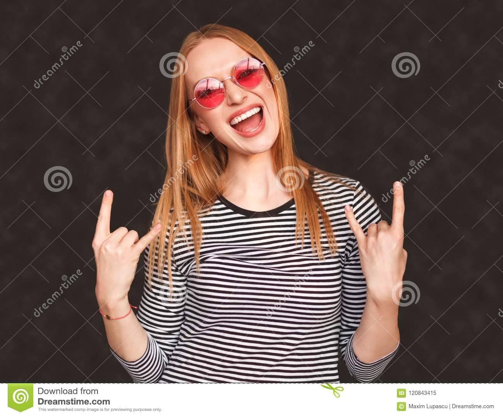 Mujer joven emocionada que muestra gesto de la roca