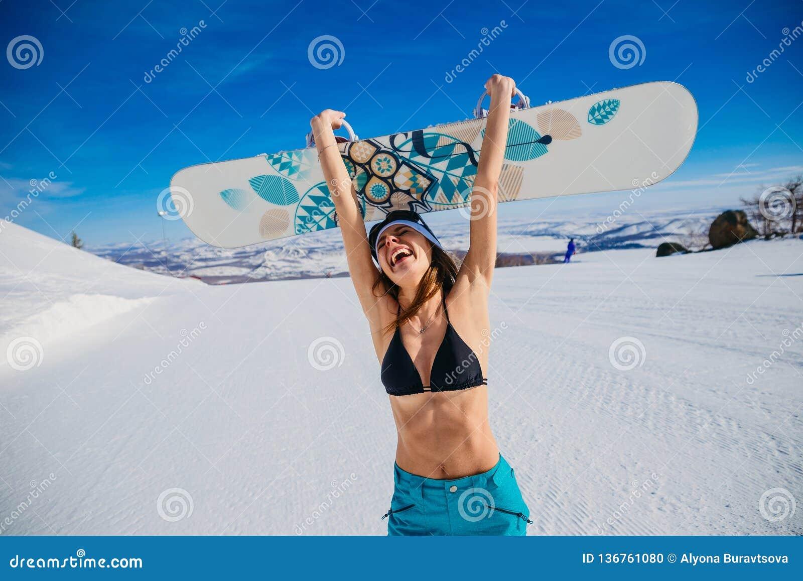 0b85a5c8e Mujer joven emocional de risa en un traje de baño y un sombrero que  sostienen una snowboard en sus manos en invierno Deporte extremo euforia  Snowboarder ...