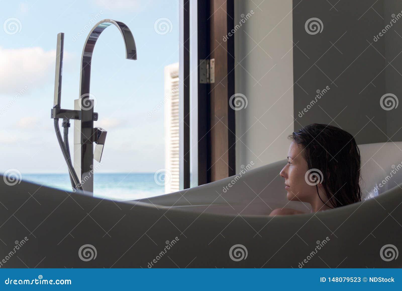 Mujer joven en bañera que admira la visión desde la ventana Destinaci?n tropical del d?a de fiesta
