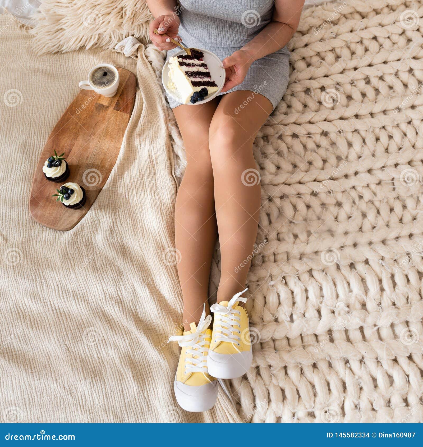 Mujer joven en cama que come las manos del desayuno que sostienen la torta sobre las piernas Café y magdalenas en la bandeja Ende