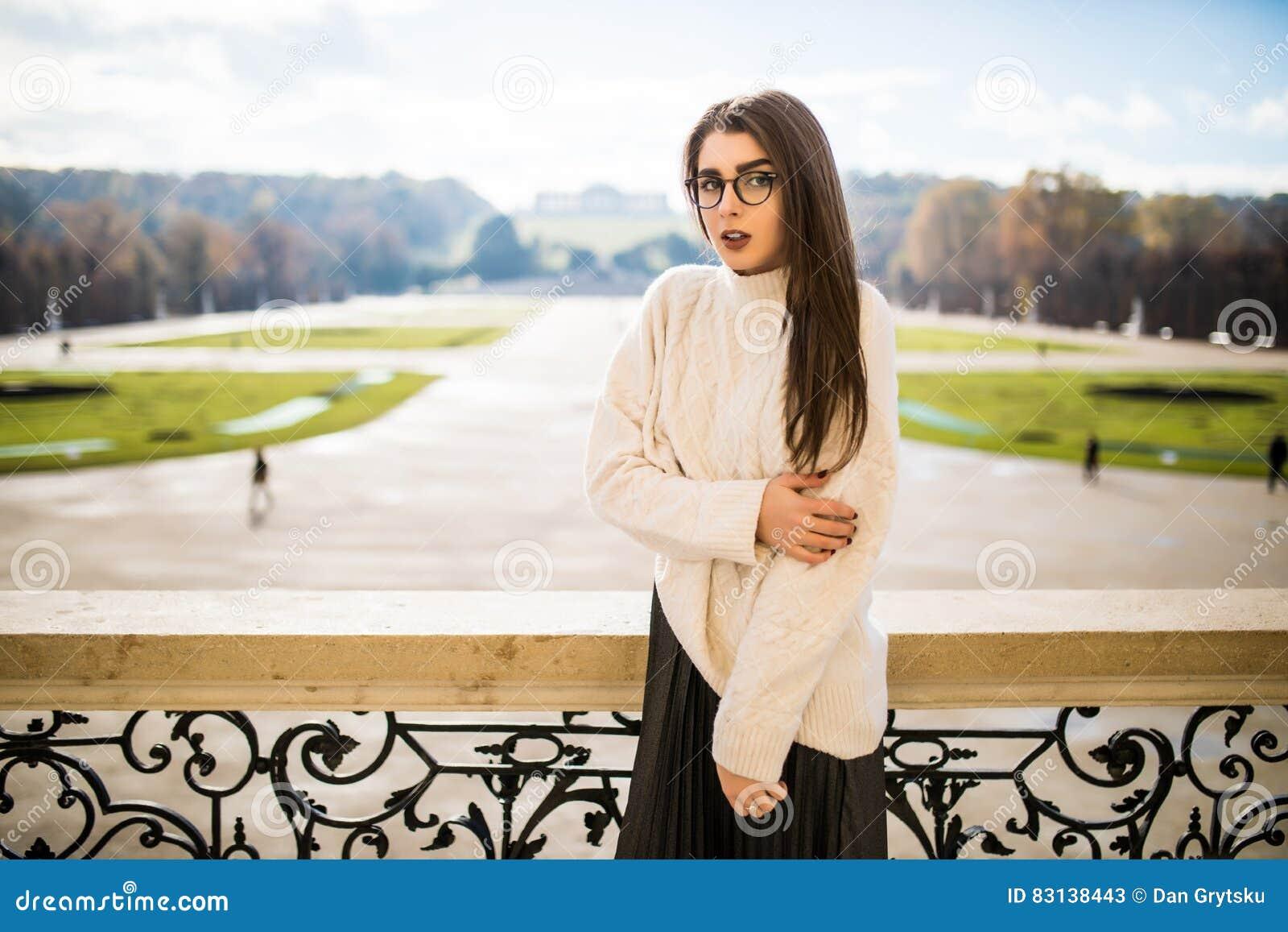 Mujer joven en el balkon de la casa en fondo del parque