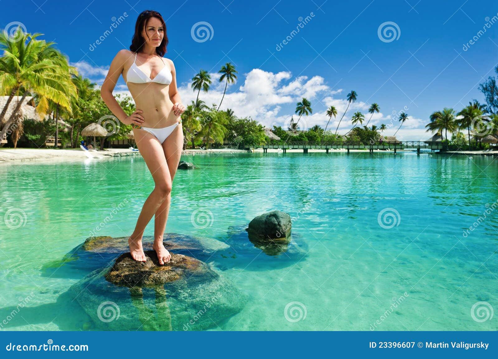 Mujer joven en el bikiní blanco que se coloca en la playa