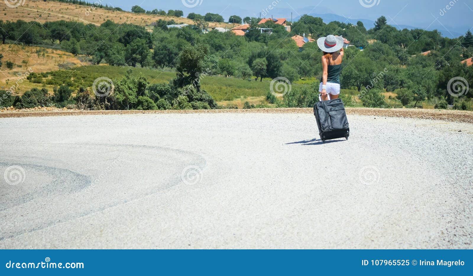 Mujer joven en el camino con equipaje