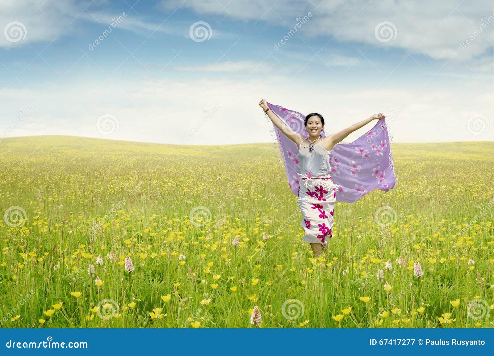 Mujer joven en el prado con la tela