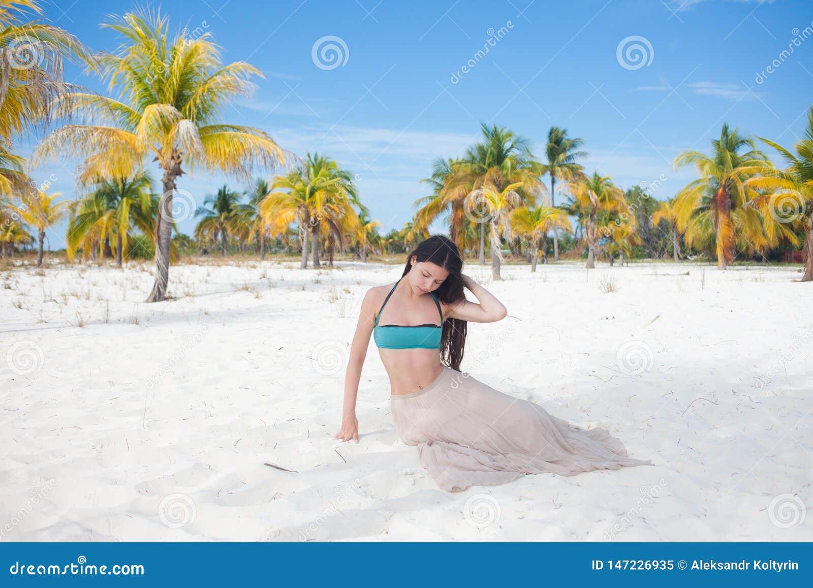 Mujer joven en el traje de baño y la falda que fluye, bailando en una playa del Caribe