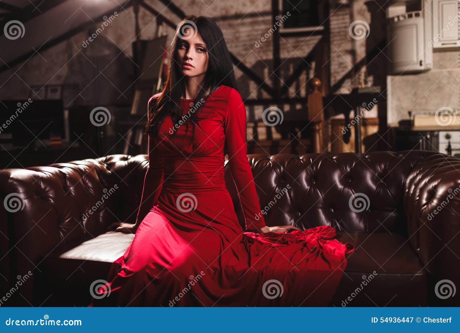 bba56ad39 Mujer morena joven sensual elegante en el vestido rojo que se sienta en el sofá  de cuero