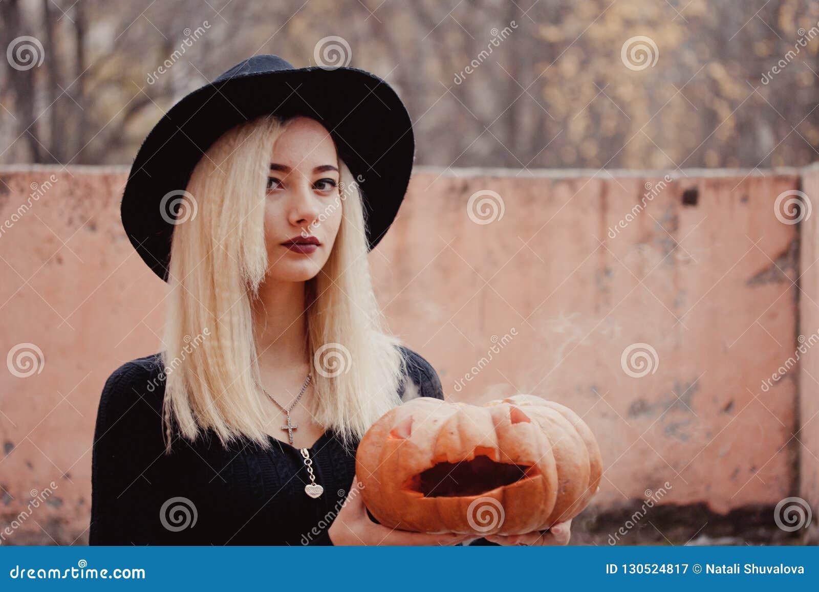 Mujer joven en la capa negra que sostiene la calabaza de Halloween con el humo blanco que viene desde adentro de él en el otoño