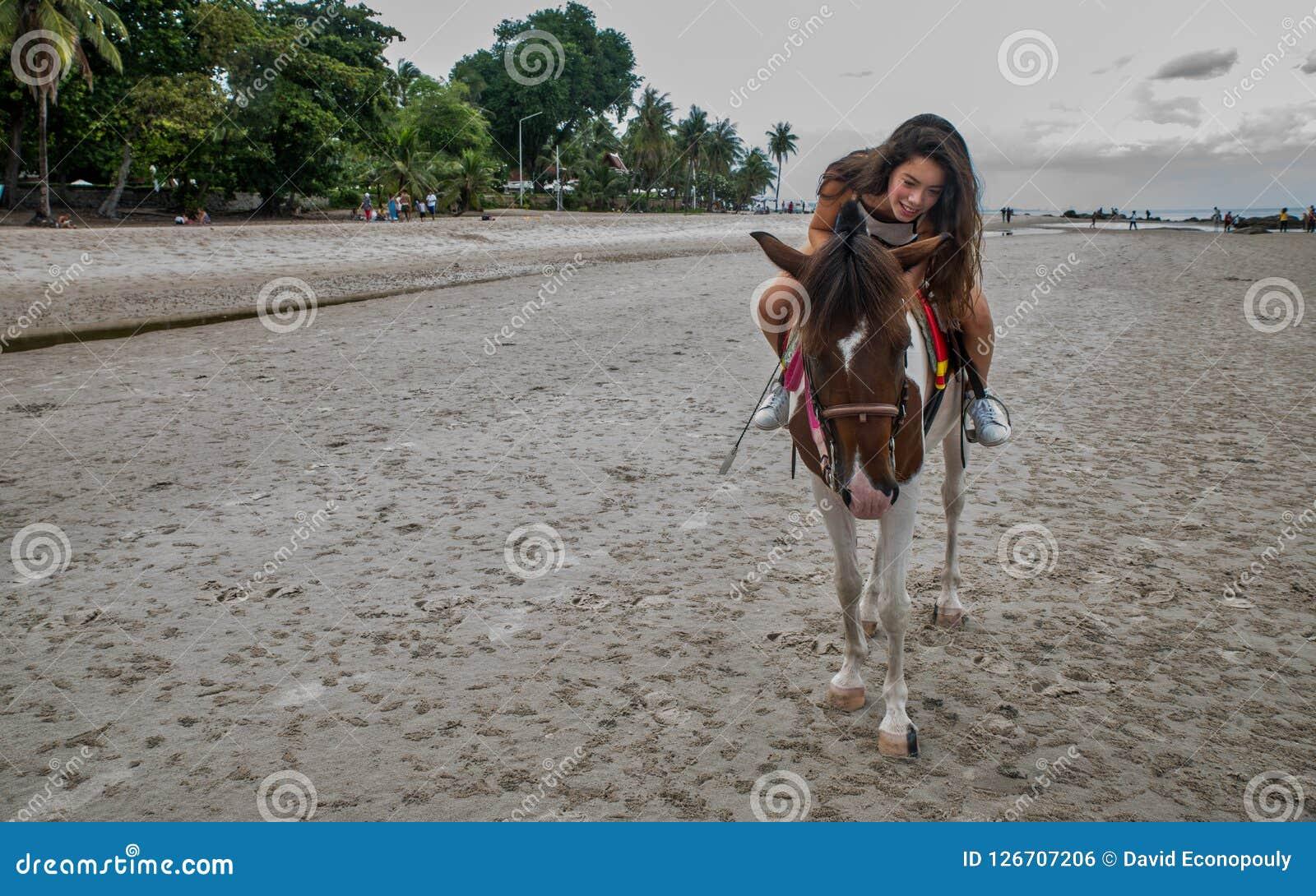 Mujer joven en la playa que abraza el caballo