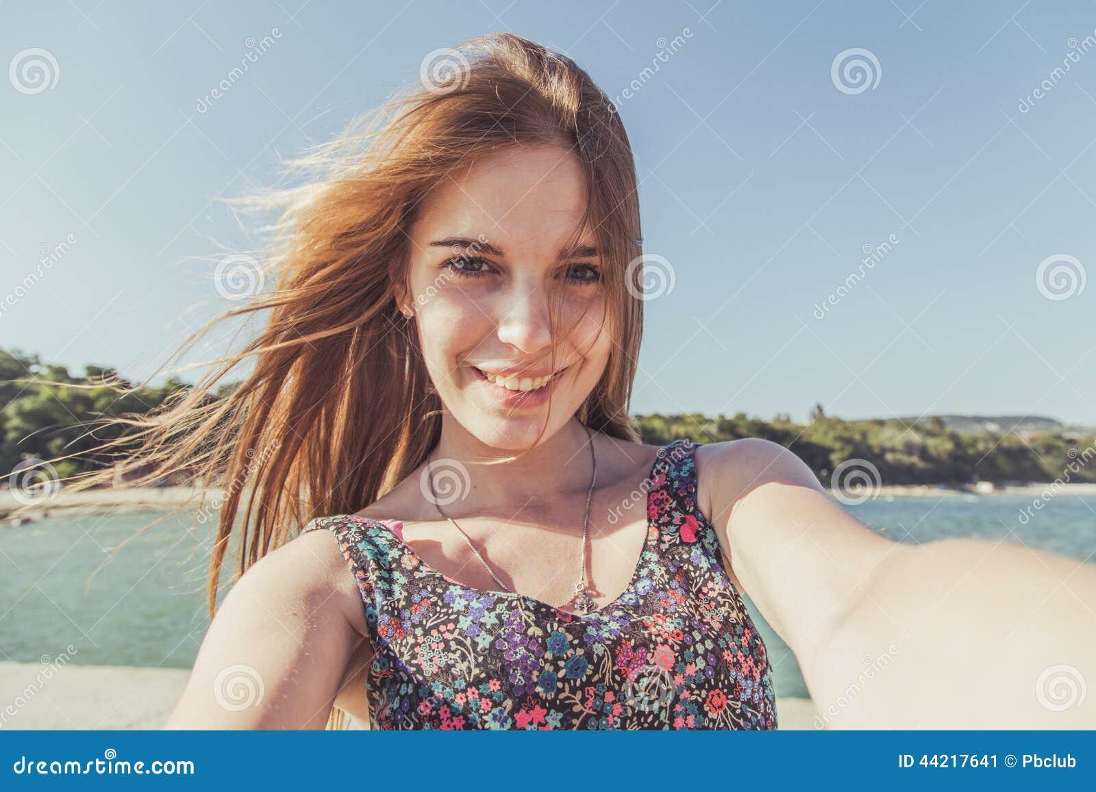 Mujer joven en la playa que mira la cámara