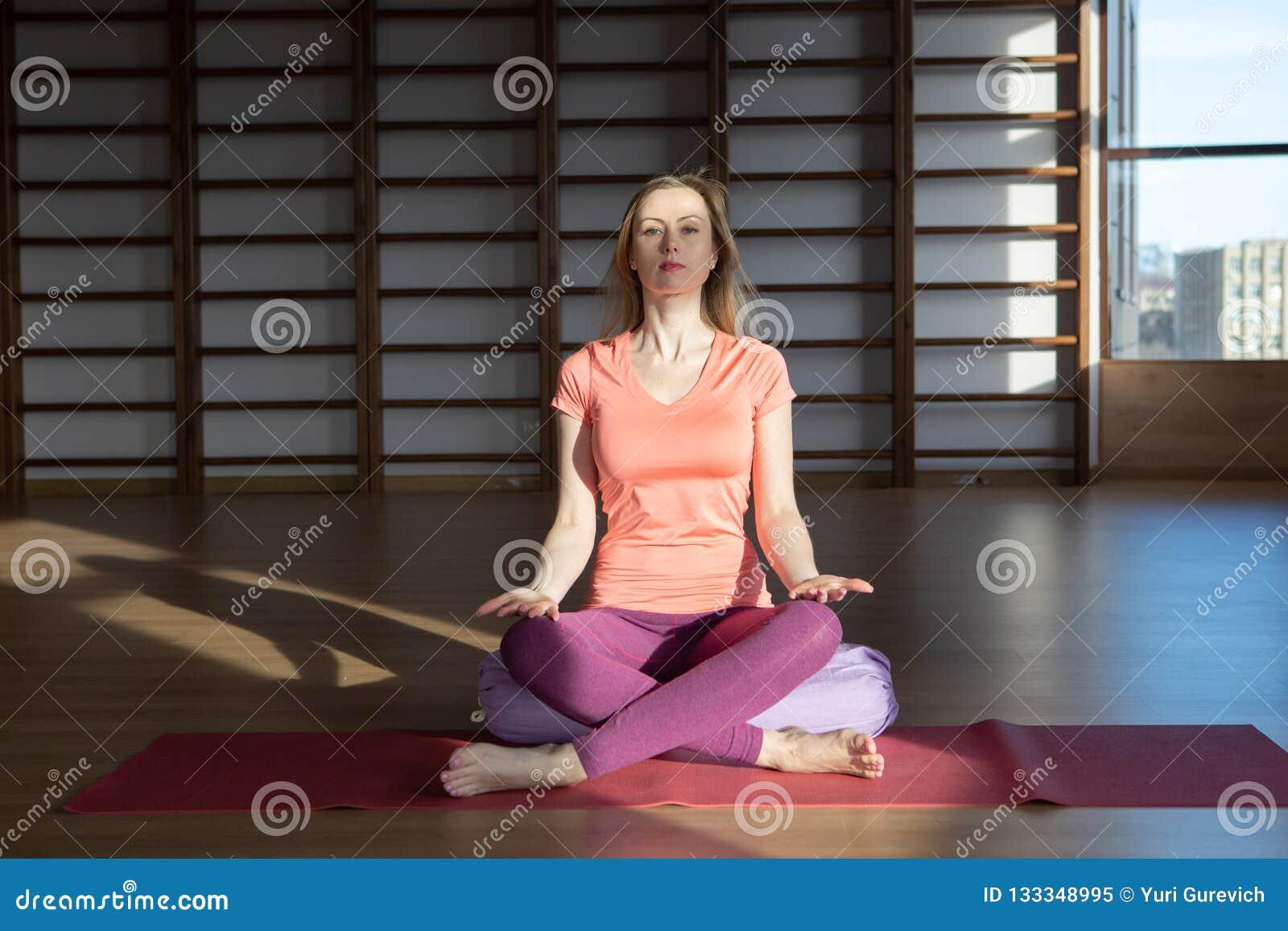Mujer joven en la posición de loto mientras que medita