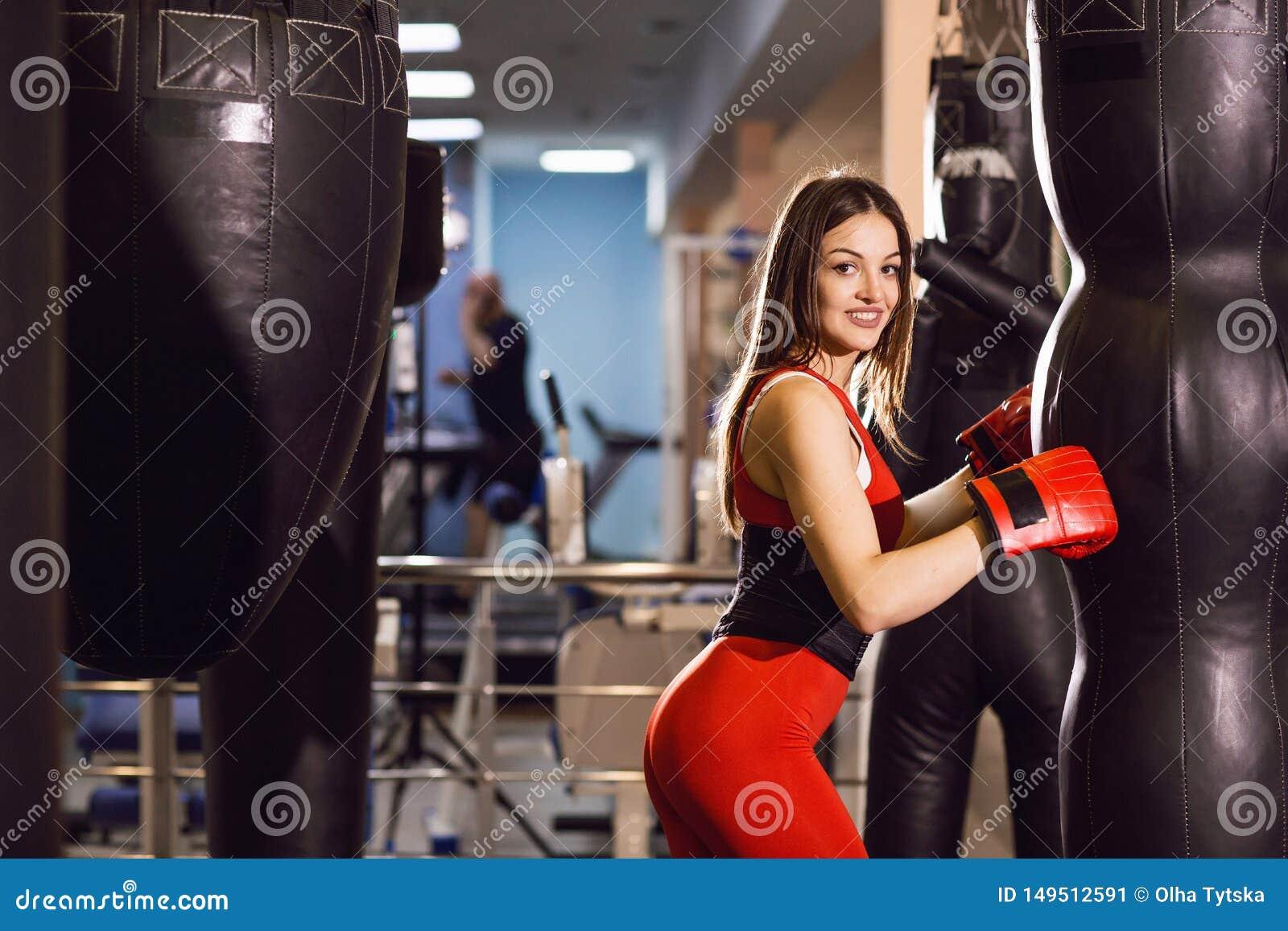 Mujer joven en la ropa y los guantes de boxeo rojos, trenes de los deportes con una pera de encajonamiento en un gimnasio oscuro
