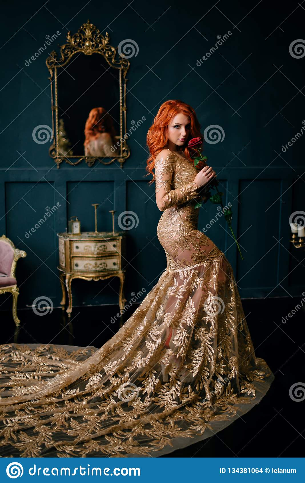 Mujer joven en la situación lujosa del vestido en interior del vintage