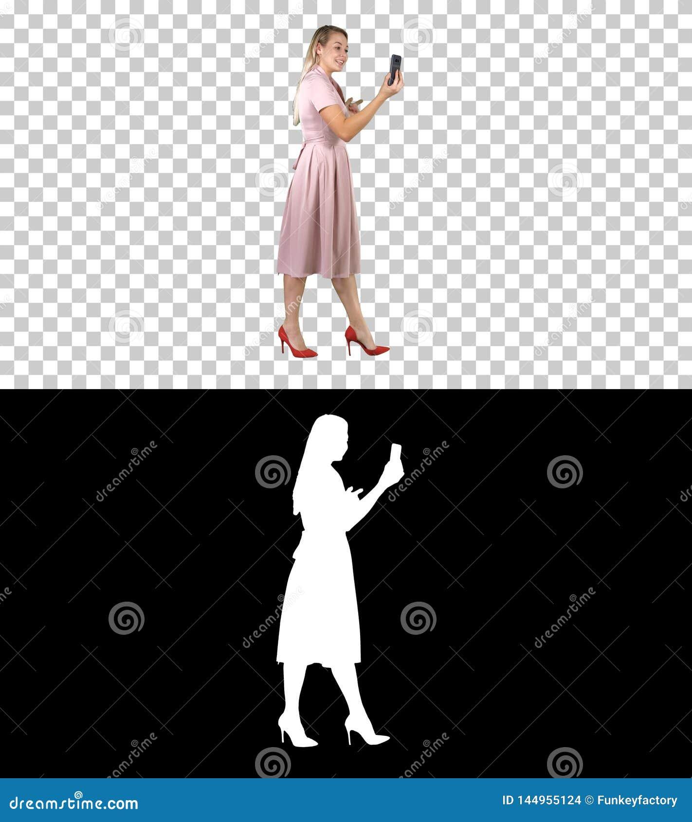 Mujer joven en la tenencia rosada usando blog video de registraci?n del tel?fono elegante mientras que camina, Alpha Channel
