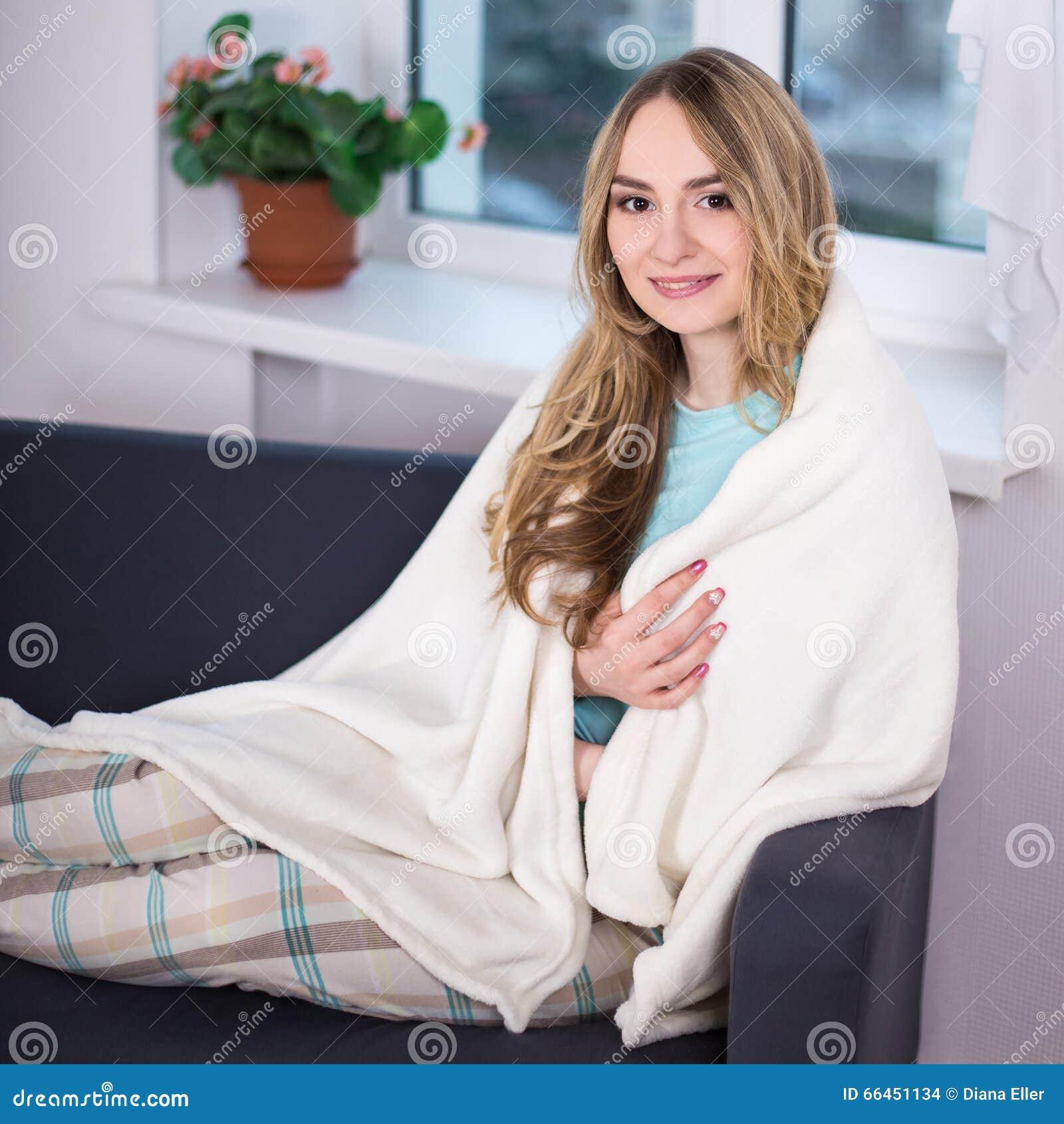 f62b42d044 Mujer hermosa joven en los pijamas envueltos en la manta que se sienta en  dormitorio