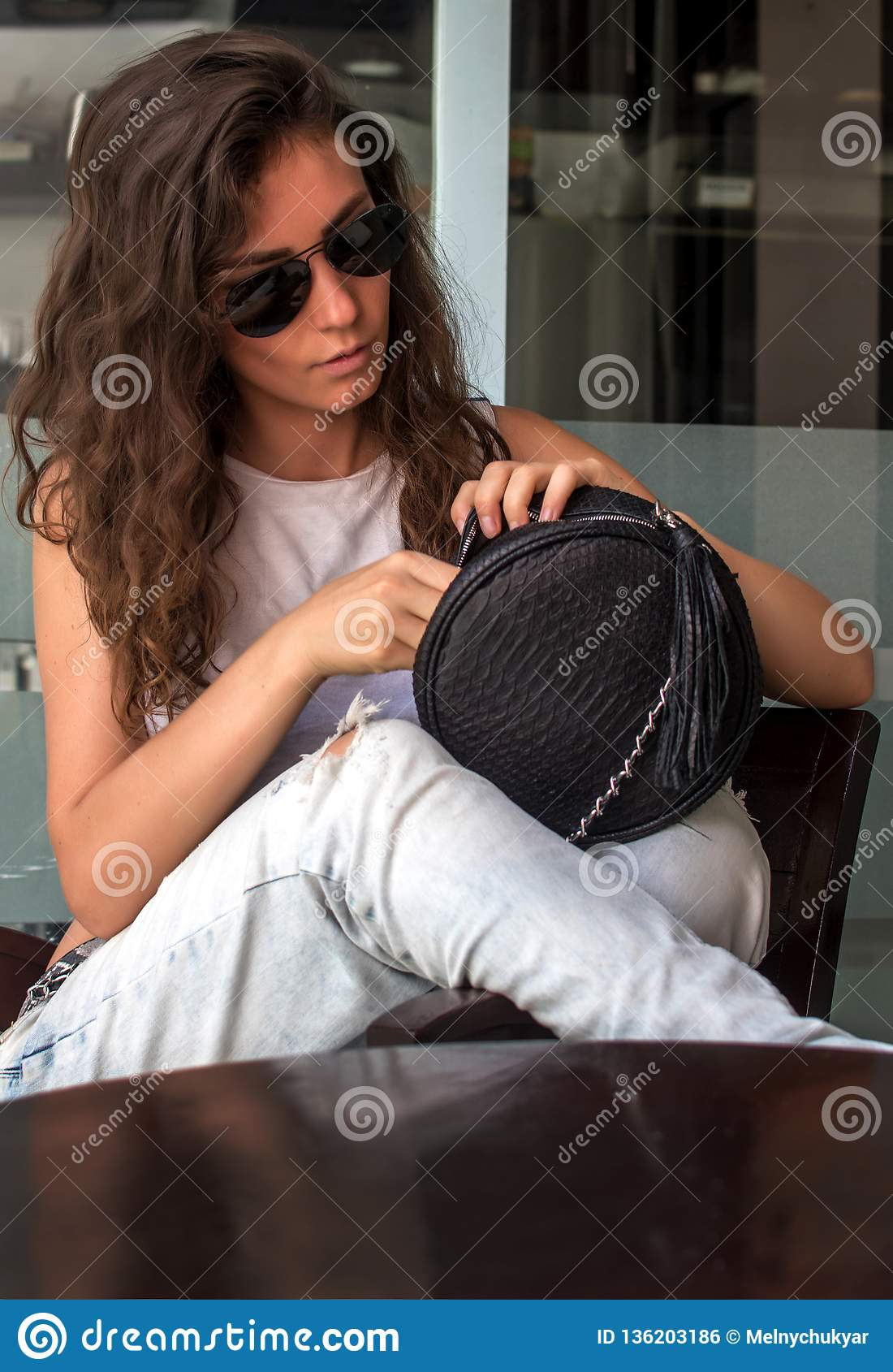 Mujer joven en los vaqueros que llevan que buscan algo en su monedero Mujer joven que mira dentro de su bolso Tenencia de moda de