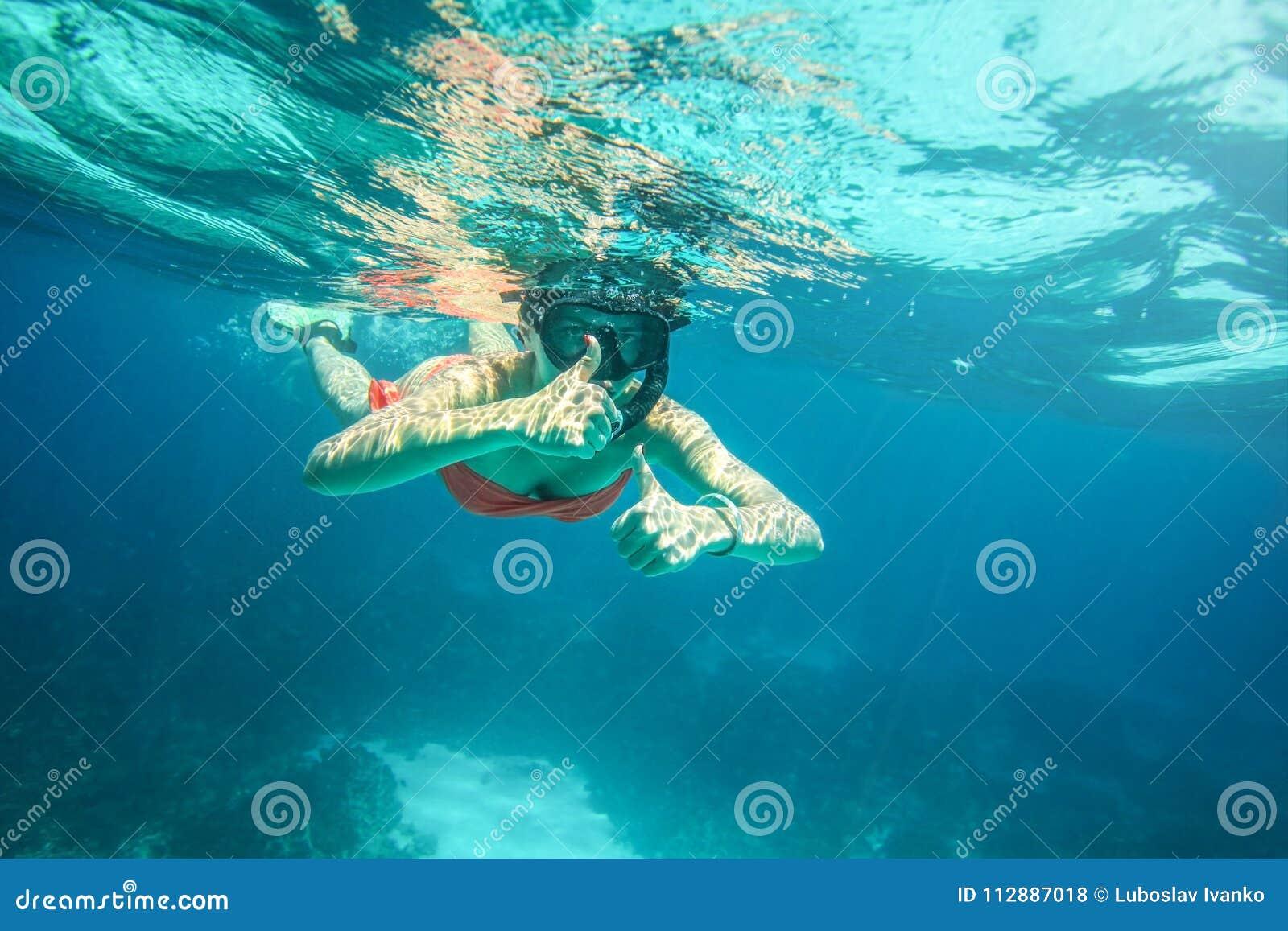 Mujer joven en máscara anaranjada del bikini y del equipo de submarinismo