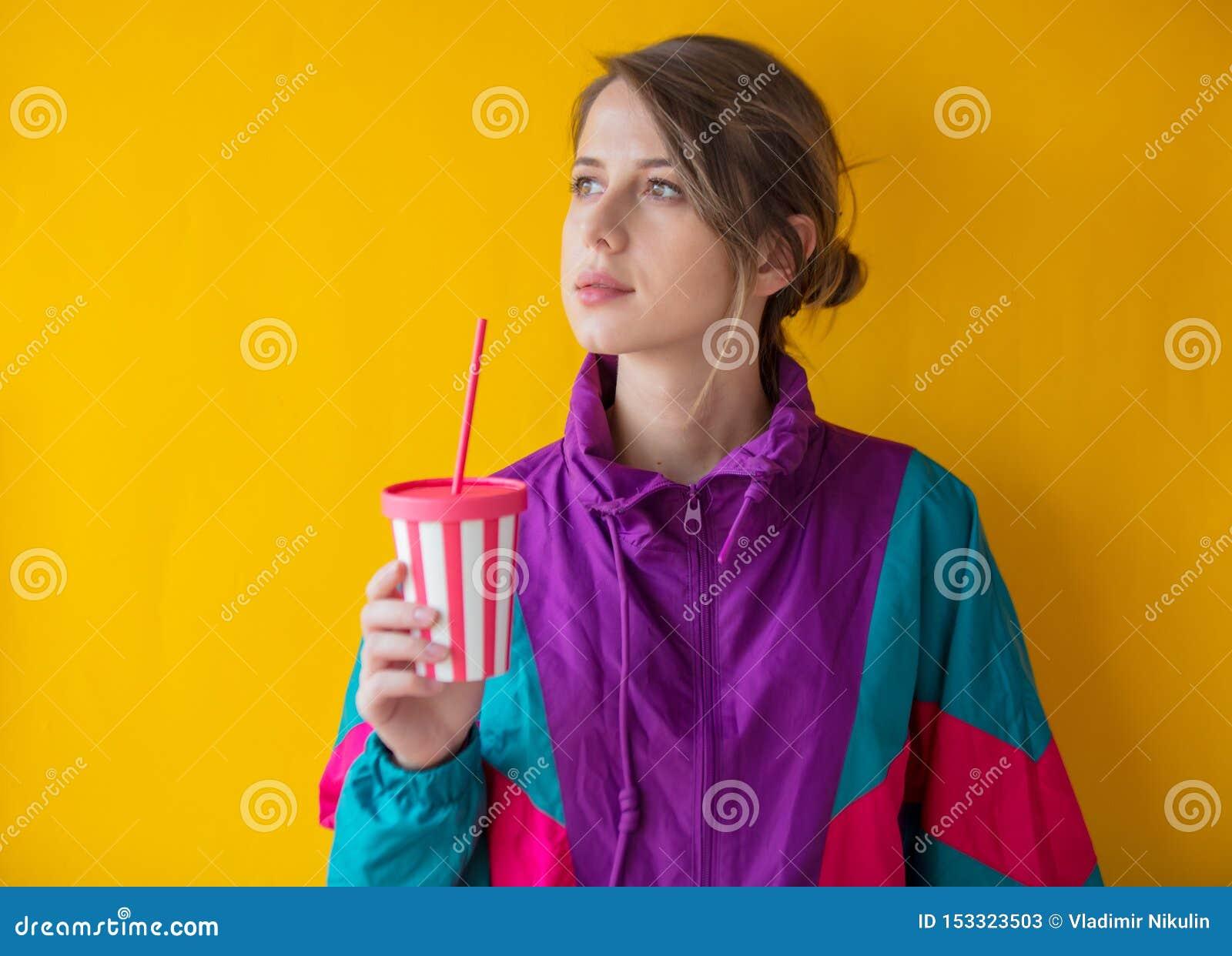 Mujer joven en ropa del estilo 90s con la taza